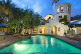 Spanish style mansion and pool at night