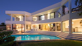 Luxury contemporary white villa, pool and garden at night