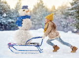 Young girl carries snowman on sled-Shutterstock