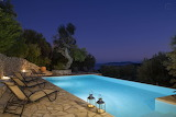 Luxury mountain and sea view pool at night in Greece