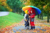 two cute boys with umbrella